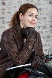 微笑的妇女画象葡萄酒褐色皮夹克的一名在街道摩托车附近的摩托车骑士和手套 免版税图库摄影