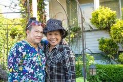 微笑的姐妹在庭院里 库存图片