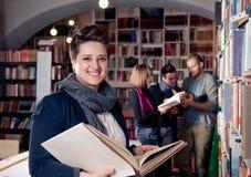 微笑的学员在图书馆里 免版税库存图片