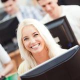 微笑的学生在计算机实验室 图库摄影