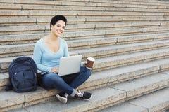 微笑的学生坐台阶使用膝上型计算机 免版税库存照片