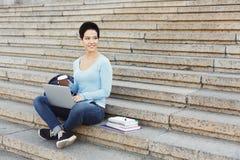 微笑的学生坐台阶使用膝上型计算机 免版税库存图片