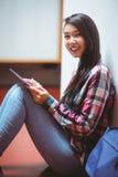 微笑的学生坐地板和使用片剂 库存照片