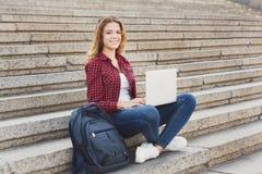 微笑的学生女孩坐台阶使用膝上型计算机户外 免版税库存照片