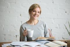 微笑的学生女孩画象书桌的,杯子在手中 免版税库存照片