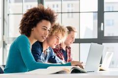 微笑的学生,当使用膝上型计算机为网上信息或v时 库存图片