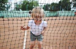 微笑的孩子的画象通过网球网 一件白色T恤杉的小逗人喜爱的女孩在网球场 免版税图库摄影