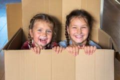 微笑的孩子看在纸板箱外面 概念移动 免版税库存图片