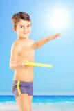 微笑的孩子简而言之投掷在海滩的飞碟在se旁边 免版税图库摄影