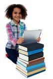 微笑的孩子繁忙与片剂个人计算机和书 库存图片