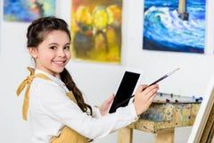 微笑的孩子绘画和使用片剂侧视图在车间  免版税库存图片