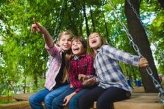 微笑的孩子获得乐趣在操场 使用户外在夏天的孩子 乘坐在摇摆的少年外面 库存照片