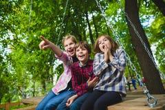 微笑的孩子获得乐趣在操场 使用户外在夏天的孩子 乘坐在摇摆的少年外面 免版税库存照片