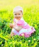 微笑的孩子晴朗的画象坐草在夏天 免版税图库摄影