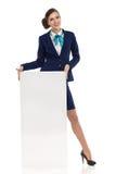 微笑的客舱乘员组妇女在海报后站立 图库摄影