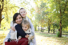 微笑的家庭一起在秋天野餐的格子花呢披肩 免版税库存照片