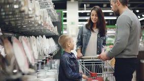 微笑的家庭买碗,并且在厨具部门的板材在大型超级市场,他们采取从架子的盘 股票录像