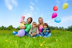 微笑的家庭坐与气球的草 免版税库存照片
