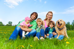 微笑的家庭坐与狗的绿草 免版税库存照片