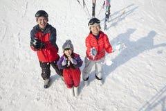 微笑的家庭投掷的雪悬而未决在滑雪胜地 免版税库存图片