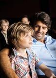 微笑的家庭观看的电影在剧院 库存照片