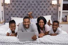 微笑的家庭画象使用膝上型计算机的,当一起说谎在床上时 免版税库存照片