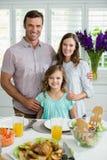 微笑的家庭画象吃午餐一起在餐桌上 库存照片