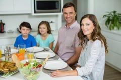 微笑的家庭画象吃午餐一起在餐桌上 免版税库存图片
