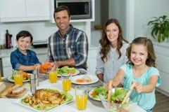 微笑的家庭画象吃午餐一起在餐桌上 免版税库存照片