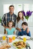 微笑的家庭画象吃午餐一起在餐桌上 免版税图库摄影