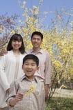 微笑的家庭画象和拿着一朵黄色花的小男孩在公园开花春天 免版税库存图片