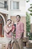 微笑的家庭画象在他们新的家前面的 免版税库存图片