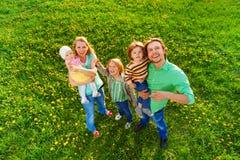 微笑的家庭画象从上面在公园 免版税图库摄影