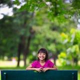 微笑的小亚裔女孩坐长凳在公园 免版税图库摄影