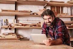 微笑的小企业主在有数字式选项的木制品演播室 免版税库存图片