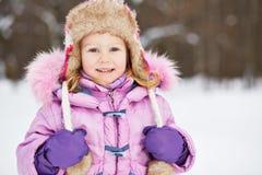 微笑的小女孩半身画象带淡红色的夹克的 免版税库存照片