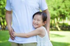 微笑的小女孩在公园拥抱父亲腰部 库存照片