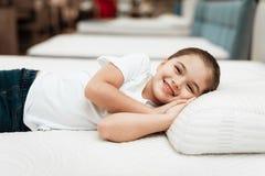 微笑的小女孩在家具店的n矫形床垫说谎 库存照片