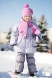 微笑的小女孩在桃红色围巾和帽子立场穿戴了 库存图片