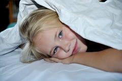 微笑的小女孩在盖子下的床上 图库摄影
