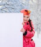 微笑的小女孩孩子在冬天给拿着一个空白的广告牌横幅白板的夹克外套和帽子穿衣 免版税库存照片