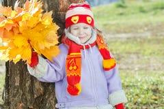 微笑的小女孩对负黄色与橙色秋叶束起手中室外画象 免版税库存图片