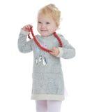 微笑的小女孩投入了她的大红色小珠 库存照片
