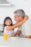 微笑的小女孩拥抱她的父亲 免版税库存照片