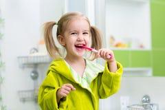 微笑的小女孩掠过的牙在卫生间里 免版税库存图片