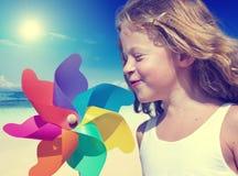 微笑的小女孩演奏海滩夏天有风概念 免版税库存照片