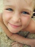 微笑的小女孩特写镜头画象海滩的 免版税库存图片