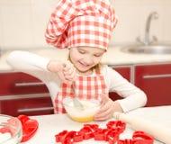 微笑的小女孩用厨师帽子stirrring的曲奇饼面团 免版税库存图片