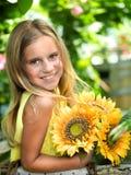 微笑的小女孩用向日葵 免版税库存图片