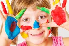 微笑的小女孩用在五颜六色的油漆绘的手 免版税库存图片